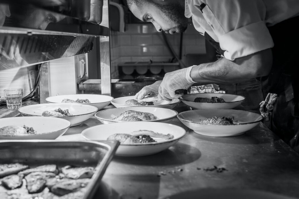 An intense chef stares down with focus on doing a task to one of many dishes of food in a commercial kitchen